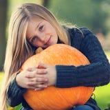 Girl with huge pumpkin stock photo