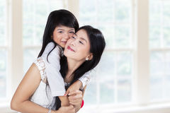 Cute girl embrace mother in home Royalty Free Stock Photography
