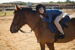 Cute girl embracing horse in the ranch. On a sunny day Stock Photography