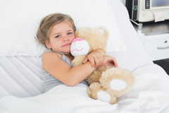 Cute girl embracing teddy bear in hospital bed Stock Photos