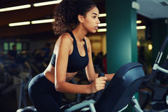 Cute girl is engaged in cardio on spinning bike at gym Royalty Free Stock Images