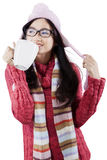 Cute girl enjoy hot drink in studio Royalty Free Stock Photography