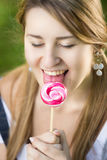 Cute girl enjoying licking red twisted lollipop Stock Image