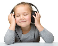 Cute girl enjoying music using headphones Stock Images