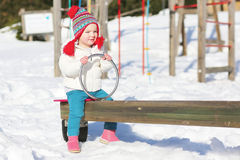 Cute girl enjoying playground at winter Stock Images