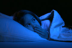 Cute girl with eyes open in bed. Cute girl with her eyes open and hand over mouth in bed Royalty Free Stock Photography