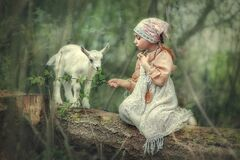 Cute girl feeds a kid of goat in the forest
