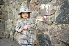 Cute girl with flower. Happy small girl wearing coat, hat and boots, holding white flower an orchid, smiling Stock Photo