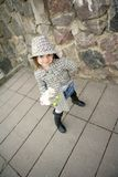 Cute girl with flower. Happy small girl wearing coat, hat and boots, holding white flower an orchid, smiling Stock Photography