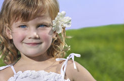 Cute girl with flower on blue sky and green grass Stock Photography