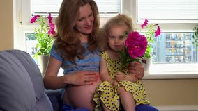 Cute girl with flower stroke her pregnant mother tummy with love. Happy family expecting brother. Static shot stock footage