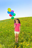 Cute girl with flying balloons stands on grass Stock Photography