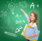 Cute girl with folders pointing to green board Royalty Free Stock Image