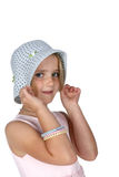 Cute girl with freckles pulling on a white hat Royalty Free Stock Image
