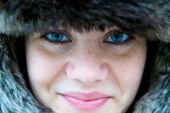 Cute girl with freckles who wear a fur hat. Incredibly cute girl with freckles with a fur hat, close-up Stock Photos