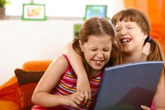 Cute girl friends laughing at laptop. Computer screen, hugging royalty free stock images