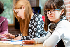 Cute girl with friends at schoolwork table. Royalty Free Stock Photography