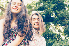 Cute girl friends sitting on a trunk Stock Photography