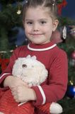 Cute girl in front of Christmas tree. Little girl sits in front of a Christmas tree holding her teddy bear Stock Image