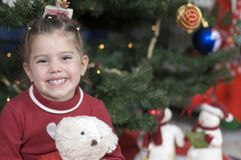 Cute girl in front of Christmas tree. Little girl sits in front of a Christmas tree holding her teddy bear Royalty Free Stock Image