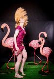 Cute girl in fuchsia sequins dress resting and dancing with three big flamingos on black background royalty free stock photography
