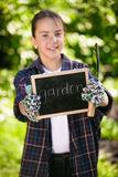 Cute girl in gardening gloves holding blackboard and tools Royalty Free Stock Image