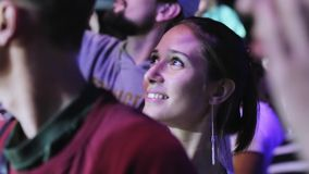 Cute girl gazes at something with amazed look being at event among other people. Happy young attractive woman at their late 20s is standing in the crowd and stock footage
