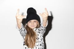 Cute girl gesturing rock at camera. Adorable girl showing devil`s horns gesture and looking at camera Stock Image