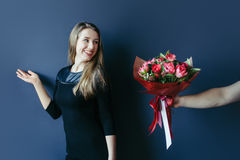 Cute girl getting bouquet of red tulips. Boyfriend giving tulips. Stock Photo