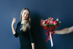 Cute girl getting bouquet of red tulips. Boyfriend giving tulips. Stock Photography