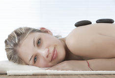 Cute girl getting a stone massage Royalty Free Stock Photos