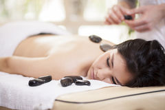 Cute girl getting a stone massage. Male therapist applying some heat with hot stones during a massage Royalty Free Stock Image