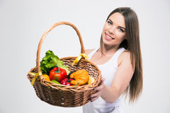 Cute girl giving basket with fruits at the camera. Portrait of a smiling cute girl giving basket with fruits at the camera isolated on a white background Stock Photo