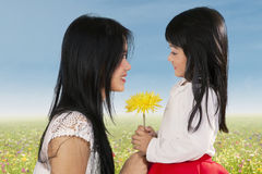 Cute girl giving flower to her mom Royalty Free Stock Photo