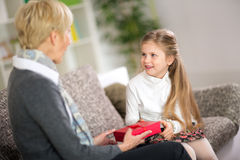 Cute girl giving her grandmother a gift Stock Image