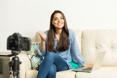 Cute girl giving a thumb up on her vlog. Portrait of a beautiful female blogger giving a thumb up while recording a video at home royalty free stock photo