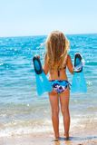 Cute girl with goggles and flippers. Cute girl in bikini facing the sea with goggles and flippers Stock Photo