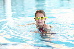 Schoolgirl with goggles in swimming pool royalty free stock photo