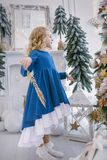 Little girl with a golden branch in her hands dancing near the Christmas tree royalty free stock photo