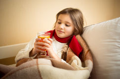Cute girl got flu and holding cup of tea at bed Royalty Free Stock Photo