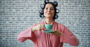 Cute girl in gown and hair rollers drinking tea smiling on brick wall background. Cute girl in gown and hair rollers is drinking tea smiling on brick wall stock video