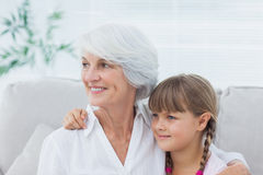 Cute girl and grandmother sitting on the couch Stock Images