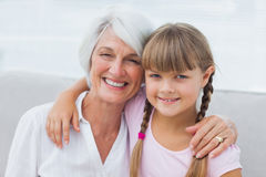 Cute girl and granny sitting on the couch Stock Photo