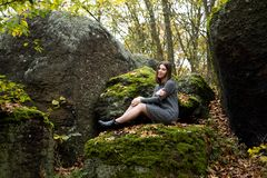 A cute girl in a gray dress sits in the fall on a moss-covered stone in the forest and smiles pleasantly. Around her lie the. Leaves turned yellow royalty free stock image