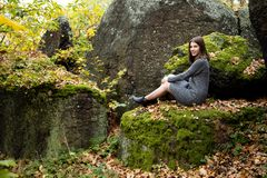 A cute girl in a gray dress sits in the fall on a moss-covered stone in the forest and smiles pleasantly. Around her lie the. Leaves turned yellow stock photos