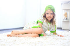 Cute girl green hat white carpet Royalty Free Stock Photo