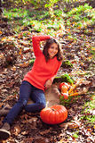 Cute girl on the ground covered with dry autumnal foliage with p Stock Images