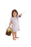 Cute girl handing flower. Cute girl in sweet dress handing blue flower, holding basket full of spring flowers, smiling Stock Photography