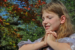 Cute Girl Hands Folded Autumn Background. This pretty little girl has her hands folded as if wishing or in prayer beneath her chin with autumn foliage in the Stock Images