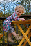 Cute Girl Hanging of Table. A cute little girl with blond hair hangs of a yellow table with a funny look on her face Stock Photo